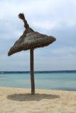Single beach umbrella. Lonely sunshade on an empty beach of Playa de Palma. Mallorca, Spain Royalty Free Stock Image