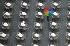 Umbrella. A person walking through tables with an umbrella Stock Photos