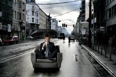 Umbrella. Businessman sitting with umbrella on armchair in a citystreet Stock Photos