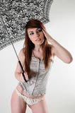 Umbrella. Female model standing under an umbrella wearing fashionable clothing looking away from the camera Royalty Free Stock Photos