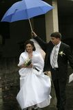 Umbrella above the young wife. The groom carefully holds a umbrella above the young wife and sees off her up to a limousine after solemn ceremony of wedding Royalty Free Stock Photos