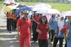In the umbrella action Commemorating Teachers' Day. Teachers are seen among the thousands of students walk down the paved road and rice fields using an umbrella Royalty Free Stock Photo