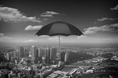 Umbrella as weather concept . Mixed media. Black umbrella flying high in sky above city Royalty Free Stock Photo
