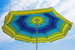 Umbrella on the beach. Umbrella in the foreground with the sky and clouds background Royalty Free Stock Photo