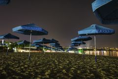 Umbrella on the beach. Blue umbrellas align on the beach at Night ,textured sand , night lights Stock Image