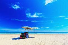 Umbrella on the beach. With cloudy blue sky in background stock photography