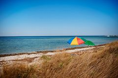 Umbrella on the beach with cloudy blue sky in background stock image
