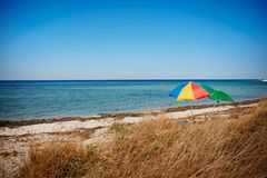 Umbrella on the beach with cloudy blue sky in background royalty free stock images