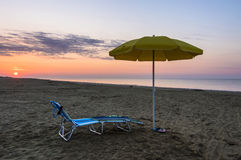 Umbrella on the beach at sunrise. Umbrella on the beach, with sun and sea on background Royalty Free Stock Image