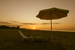 Umbrella on the beach at sunset. Umbrella on the beach, with sun and sea on background Stock Photography