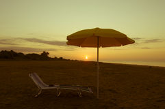 Umbrella on the beach at sunset. Umbrella on the beach, with sun and sea on background Royalty Free Stock Photos