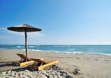Umbrella on beach. Two wooden deckchairs under straw parasol on sandy beach Royalty Free Stock Photos
