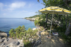 The umbrella and  bench on picturesque shore of the black sea. Stock Image