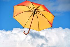 Umbrella. On a blue sky above clouds stock images