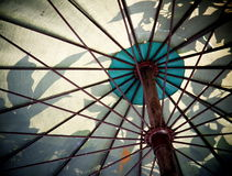 Umbrella. Bottom view under a large old aged weathered dirty gray  green color canvas umbrella with rustic metal construction Stock Photo
