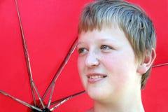Umbrella Boy. Boy with a red umbrella behind him, taken outdoors stock image