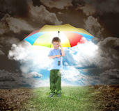 Umbrella Boy with Rays of Sunshine and Hope. A young child is holding a rainbow umbrella with sunshine glowing out. The boy is surrounded with a dried up Royalty Free Stock Image