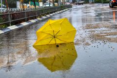 Winter weather in Israel: umbrella, rain, puddles with water circles and floods. An umbrella broken by the wind with raindrops on the wet asphalt road. Winter royalty free stock photos