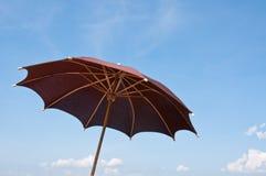 Umbrella. Brown umbrella on blue sky Stock Images