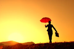 Umbrella business woman and sunset silhouette Stock Photos