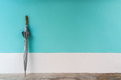 Umbrella on cement floor with pastel wall background. Royalty Free Stock Photos