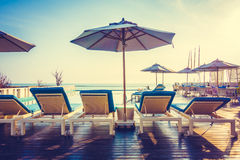Umbrella and chair around swimming pool Stock Image