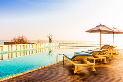 Umbrella and chair around swimming pool Royalty Free Stock Photos