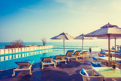 Umbrella and chair around swimming pool Royalty Free Stock Photo