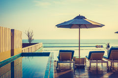 Umbrella and chair around swimming pool Stock Photo