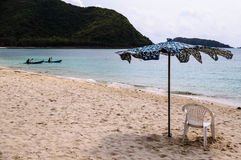 Umbrella and chair on beach Stock Images