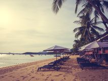 Umbrella and chair on the tropical beach sea and ocean at sunris royalty free stock photo