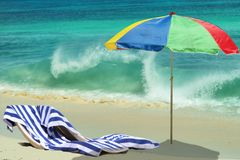 Umbrella, chairs on beach. Playing sea wave. The colorful umbrella, chairs are waiting on the tropical beach. Beautiful foamy wave is crushing down on the sea Royalty Free Stock Photos