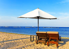 Umbrella and chaise lounges on a beach. Stock Photography