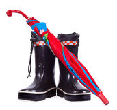 Umbrella on the children rain boots Royalty Free Stock Image