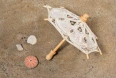 Umbrella cloth. On the sand with shells Stock Photos