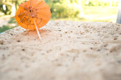 Umbrella for cocktails on a sandy summer background. stock photo