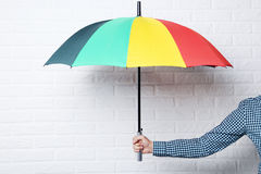 Umbrella. Colorful umbrella in male hand on brick wall background Stock Photos