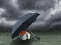 Umbrella covering home under heavy rain. Insurance concept Stock Image