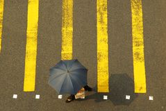 Umbrella Crossing 1. Woman crossing the street at a busy intersection royalty free stock image