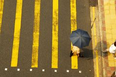 Umbrella Crossing 2. Woman crossing the street at a busy intersection Royalty Free Stock Photo