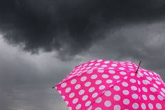 Umbrella with dark clouds Stock Photos