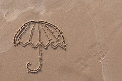 Umbrella drawn in the sand. Beach background. Stock Images
