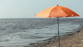 Umbrella on an empty beach. Seascape stock video footage