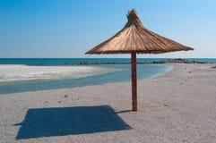 Umbrella  on empty beach Stock Photos