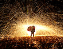 Umbrella and fire. A woman holds and umbrella with fire sparks flying around her Royalty Free Stock Photo