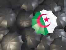 Umbrella with flag of algeria. On top of black umbrellas. 3D illustration Stock Photos