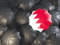 Umbrella with flag of bahrain. On top of black umbrellas. 3D illustration Royalty Free Stock Photo