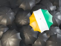 Umbrella with flag of cote d`Ivoire. On top of black umbrellas. 3D illustration Stock Photos