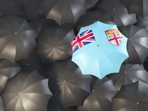 Umbrella with flag of fiji. On top of black umbrellas. 3D illustration Stock Photos