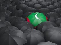 Umbrella with flag of maldives. Over black umbrellas Stock Photos